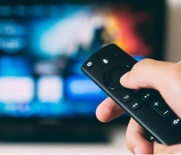Hand turning on TV with remote control